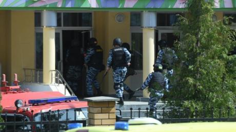 Rettungswagen und Polizeifahrzeuge mit Blaulicht und Sirene: der Tatort in der russischen StadtKasan nach dem tödlichen Angriff.