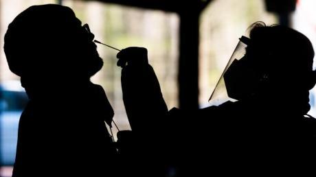 Helfer testen einen Mann im «Testzentrum am Zoo» in Hannover mit einem Schnelltest auf das Coronavirus.