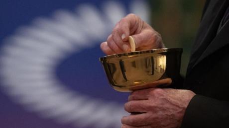 Ein Mitglied der Kirchengemeinde hält während eines Gottesdienstes mit Abendmahl im katholischen Dom St. Bartholomäus vor dem Logo des ÖKT eine Oblate in der Hand.