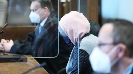 Die angeklagte Mutter (M) zwischen Anwälten im Gerichtssaal in Köln.