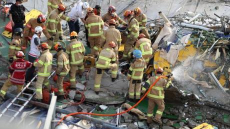 Feuerwehrleute suchen nach Überlebenden in dem eingestürzten Gebäude in Südkorea.