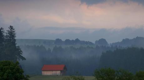 Eine Holzhütte steht im Abendlicht in der wolkenverhangenen Allgäuer Landschaft bei Marktoberdorf. (Archivbild).