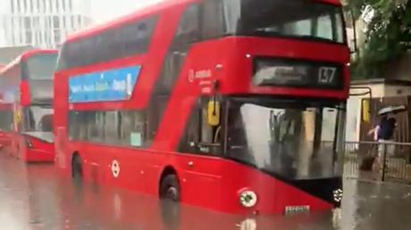 Ein Londoner Bus auf einer überschwemmten Straße.