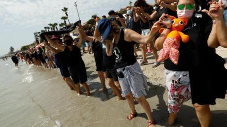 Demonstranten und Demonstrantinnen bilden eine mehr als 73 Kilometer lange Menschenkette am Ufer des Mar Menor.