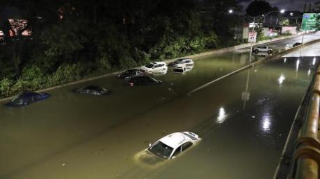 Fahrzeuge stehen im Hochwasser auf einer Straße New Yorks.
