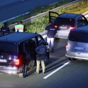 Polizisten stehen mit ihren Fahrzeugen auf der Autobahn 9.