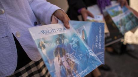 Zeugen Jehovas verteilen Hefte. Die Religionsgemeinschaft will eine Gleichstellung mit anderen Kirchen. Foto: Matthias Balk/Archiv