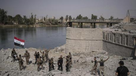 Irakische Spezialeinheiten feiern am Ufer des Tigris den Sieg über die IS-Anhänger in Mossul. Foto: Felipe Dana/Archiv