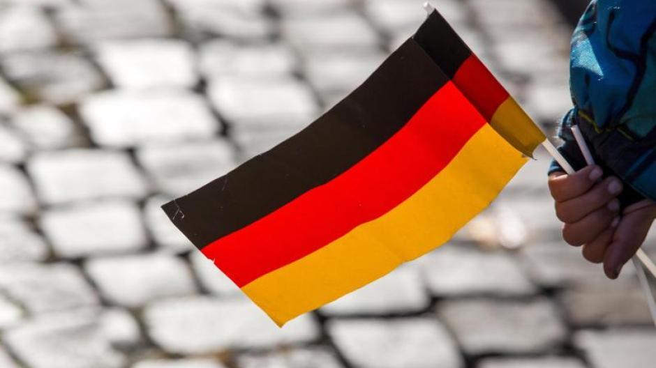 Ein Kind hält eine Deutschlandflagge. In Mainz beginnt das Bürgerfest zum Tag der Deutschen Einheit.