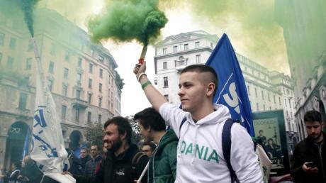 Aktivisten der rechtspopulistischen Partei Lega halten bei einer Demonstration in Mailand Rauchfackeln in die Höhe.