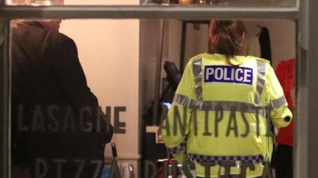 Polizisten halten sich in einem Restaurant auf, das in Verbindung mit der Vergiftung eines Ex-Agenten stehen soll und daraufhin geschlossen wurde.