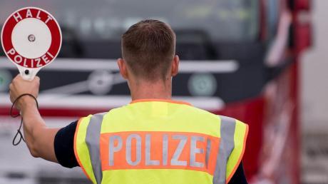 Ein Polizist kontrolliert einen LKW.