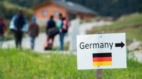 Flüchtlinge gehen nahe der deutschen Grenze hinter einem Schild mit der Aufschrift «Germany».