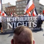 Vor dem Zug der Neonazi-Demonstration anlässlich des 31. Todestages von Rudolf Heß kniet ein Mann mit einer Fisur, die bei Neonazis üblich ist. Foto: dpa