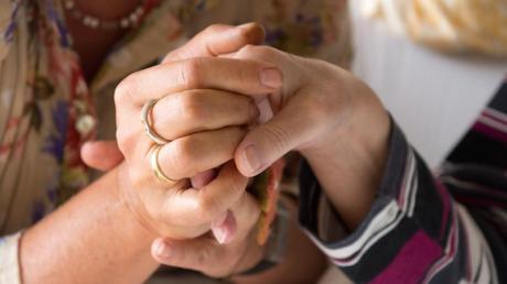 Eine Therapeutin hält in einem Hospiz in Stuttgart die Hand einer todkranken Bewohnerin. Foto: Sebastian Kahnert