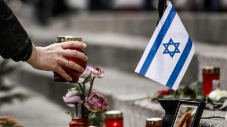 Eine Frau zündet am Breitscheidplatz am Mahnmal vor einer israelischen Fahne ein Kerzenlicht ab. Foto: Carsten Koall