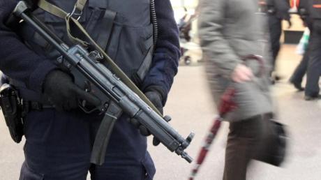 Ein bewaffneter Polizist mit Sicherheitsweste in einem Bahnhof: Die Terrorgefahr im Land ist weiter hoch. Foto: Bodo Marks