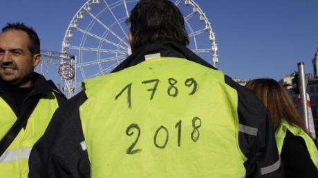 Ein Demonstrant der «Gelbwesten» hat die Jahreszahlen «1789» und «2018» auf seine Weste geschrieben in Anlehnung an die Französische Revolution von 1789. Foto: Claude Paris/AP