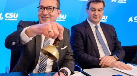 Alexander Dobrindt (l), CSU-Landesgruppenchef, läutet neben Markus Söder, Ministerpräsident von Bayern, ein Glöckchen zur Eröffnung der Winterklausur.