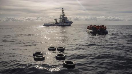 Migranten sitzen in einem Schlauchboot, nachdem sie im Mittelmeer entdeckt und gerettet wurden. Foto: Olmo Calvo/AP