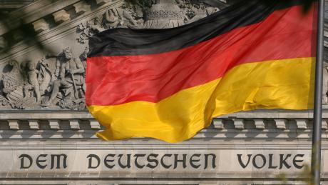 Die Deutschland-Fahne weht vor dem Reichstag in Berlin, auf dem der Spruch «Dem deutschen Volke» zu lesen ist.