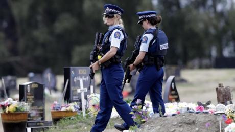 Bewaffnete Polizisten patrouillieren in der Nähe von muslimischen Gräbern auf einem Friedhof in Christchurch. Foto: Mark Baker/AP