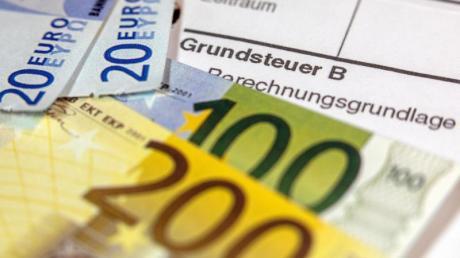 Euro-Geldscheinen liegen auf einem Abgabenbescheid für die Entrichtung der Grundsteuer. Foto: Jens Büttner/Archivbild