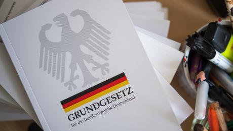Eine Ausgabe des Grundgesetzes der Bundesrepublik Deutschland liegt auf einem Tisch neben Schreibutensilien. Am 23. Mai wird das Grundgesetz 70 Jahre alt.