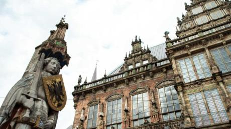 Ein Blick auf den Roland (l) neben dem Alten Rathaus in Bremen.