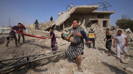 Ein Mann trägt ein Kind, das aus einem zerstörten Haus gerettet wurde, aus der Gefahrenzone. Die Region Idlib ist seit Wochen Ziel heftiger Attacken der Luftstreitkräfte Assads und seiner Verbündeten.