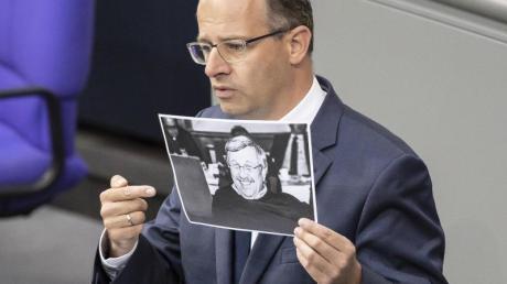Michael Brand (CDU) hält bei seiner Rede im Bundestag ein Bild des ermordeten Kasseler Regierungspräsidenten Walter Lübcke. Foto: Christoph Soeder