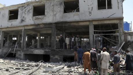 Afghanische Männer suchen nach dem Anschlag nach persönlichen Gegenständen in ihren Läden.