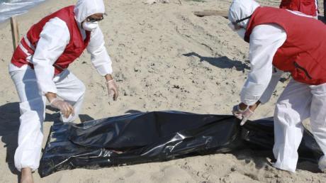Libysche Mitarbeiter des Roten Halbmonds bergen die Leiche eines ertrunkenen Migranten. Foto: Hazem Ahmed/AP