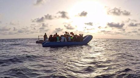 Das von der Seenotrettungsorganisation Sea-Eye herausgegebene Foto vom Mittwoch zeigt Seenotretter der «Alan Kurdi» vor einem Schlauchboot voller Flüchtlinge. Foto: Pavel D. Vitko/Sea-Eye