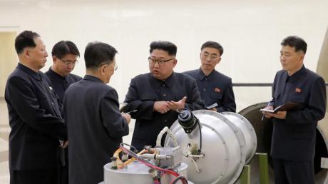 Nordkoreas Staatschef Kim Jong Un neben einem Sprengkopf.