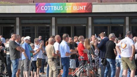 Teilnehmer des Wahlkampfauftakts der AfD-Jugendorganisation Junge Alternative stehen vor einem Transparent an der Stadthalle mit der Aufschrift «Cottbus ist bunt».