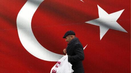 Ein Mann geht an einer türkischen Flagge vorbei.