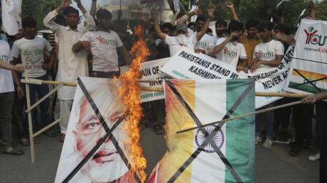 Pakistanische Demonstranten verbrennen bei einer Kundgebung in Lahore eine Fahne mit dem Bild des indischen Premierministers Modi.