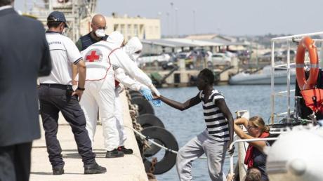 Migranten verlassen im Hafen von Pozzallo auf Sizilien das deutsche Rettungsschiff Eleonore. Foto: Francesco Ruta/ANSA