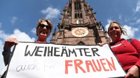 Zwei Frauen der Initiative Maria 2.0 werben vor dem Freiburger Münster für «Weiheämter auch für Frauen». Foto: Patrick Seeger