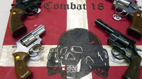 """""""Combat 18"""" gilt als gewaltbereit. Das Bild zeigt sichergestellte Waffen und ein Schild der Neonazi-Gruppe im schleswig-holsteinischen Landeskriminalamt."""