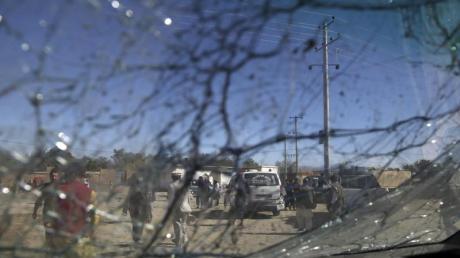 Afghanische Männer und Sicherheitskräfte in Tscharikar, wo ein Selbstmordattentäter bei einer Wahlkampfveranstaltung desPräsidenten Ghani mehr als 20 Menschen getötet hat.