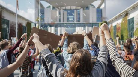 Teilnehmer einer Fridays for Future-Demonstration bilden eine Menschenkette vor dem Kanzleramt.