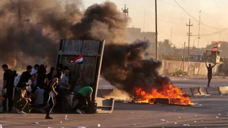 Regierungsfeindliche Demonstranten haben während einer Demonstration in Bagdad Feuer gelegt und eine Straße blockiert. Foto: Khalid Mohammed/AP/dpa