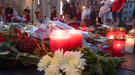 Menschen kommen nach einem ökumenischen Gedenkgottesdienst für die Opfer des Terroranschlags in Halle vor der Marktkirche in Halle (Saale) zusammen und stellen Kerzen ab. Foto: Hendrik Schmidt/dpa-Zentralbild/dpa