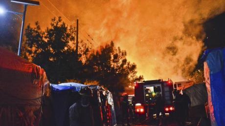 Feuerwehrleute kämpfen gegen den Brand in dem überfüllten Migrantenlager. Foto: Michael Svarnias/AP/dpa