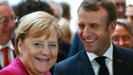 Demonstrative Geste: Bundeskanzlerin Angela Merkel und der französische Präsident Emmanuel Macron während eines Besuchs einer Airbus-Montagehalle in Toulouse. Foto: Frederic Scheiber/AP/dpa
