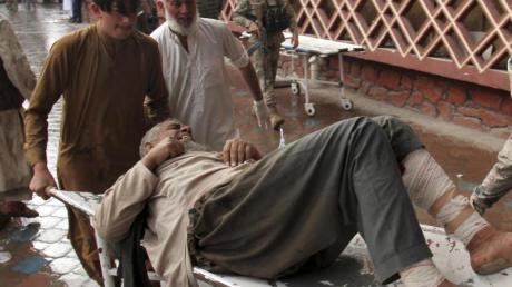 Ein verwundeter Mann wird mit einer Trage in ein Krankenhaus gebracht. Foto: Wali Sabawoon/AP/dpa