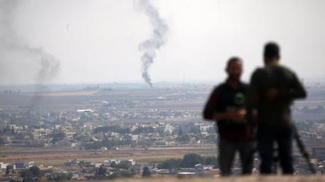TV-Journalisten beobachten von einer Anhöhe auf der türkischen Seite der Grenze aus Rauch über dem nordsyrischen Ras al-Ayn. Foto: Lefteris Pitarakis/AP/dpa
