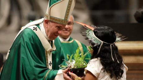 Ein Mädchen aus dem Amazonas-Gebiet überreicht Papst Franziskus während der Abschluss-Messe der Bischofssynode eine Pflanze.